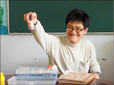 腦麻教師益宏拿著教具靦腆的笑著|礙的萬物論